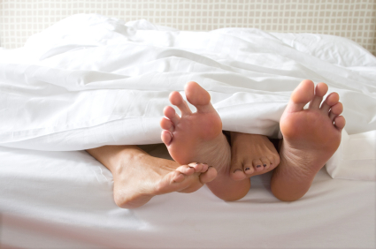 Woman and man's feet sticking out of the bed covers