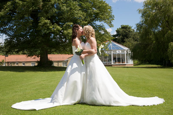 lesbian couple in wedding dresses getting married kissing