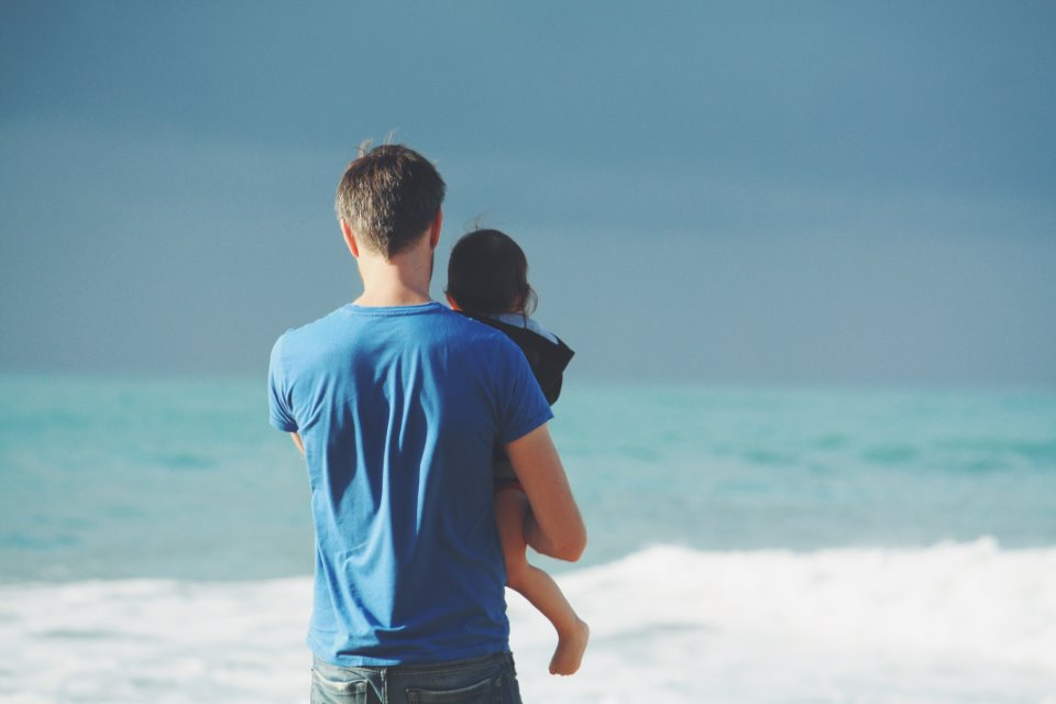 sperm donor holding child on a beach
